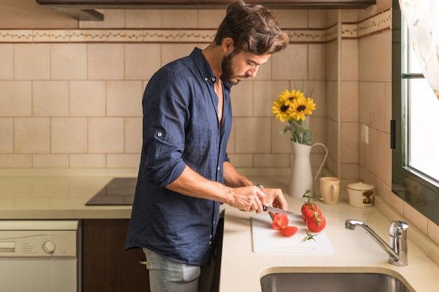 Young man cutting slice of tomatoes on white chopping board