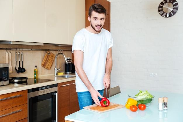 台所で野菜を切る若い男