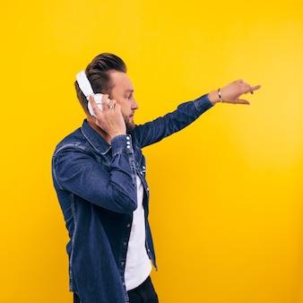 젊은 남자 춤과 음악 듣기. 감정, 표정, 감정, 신체 언어, 표지판. 노란색 스튜디오 배경 이미지입니다.