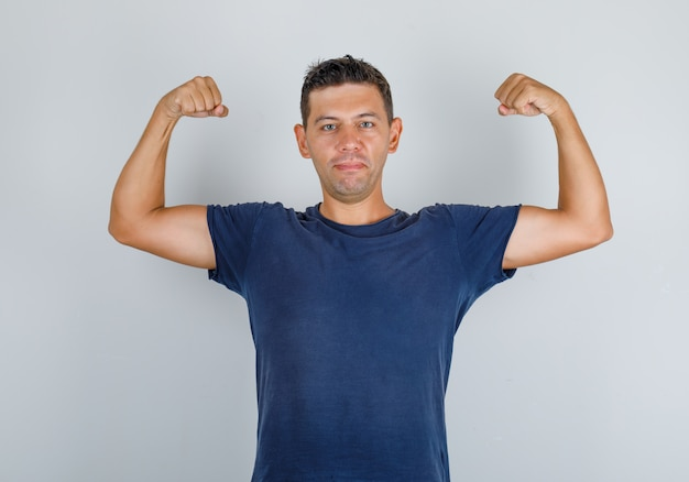 Young man in dark blue t-shirt showing muscles and looking strong, front view.