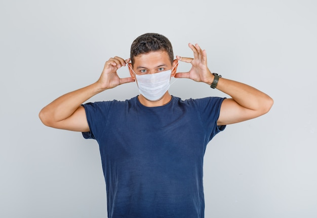 Young man in dark blue t-shirt wearing medical mask and looking careful, front view.