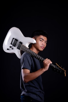 Young man in dark t shirt with electric guitar