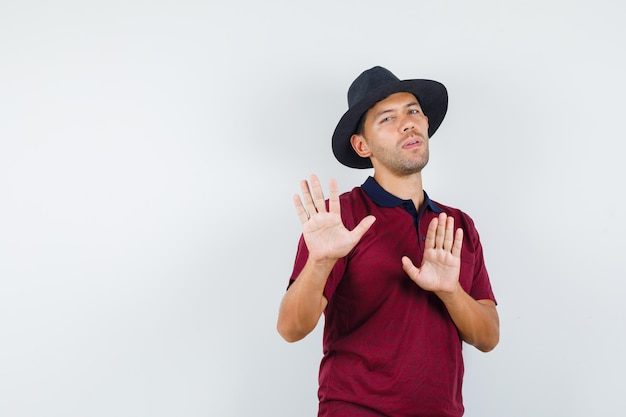 Young man defending himself by raising palms in t-shirt, hat and looking scared , front view.