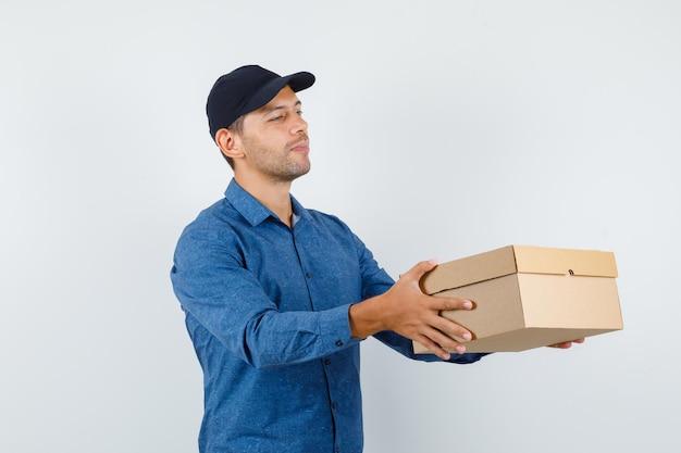 파란색 셔츠, 모자, 쾌활한 찾고 골 판지 상자를 배달 하는 젊은 남자. 전면보기.