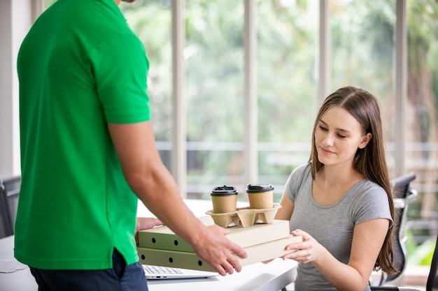 문간에서 고객에게 음식을 배달하는 청년, 야외에서 웃고 있는 배달원의 손에 종이 주머니, 음식 용기. 레스토랑의 품질 서비스.