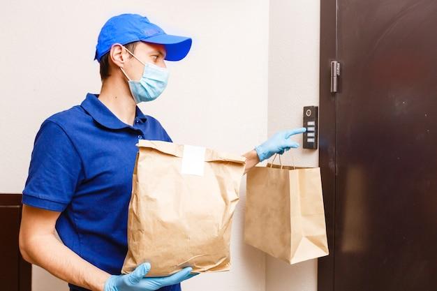 戸口で顧客に食べ物を配達する若い男