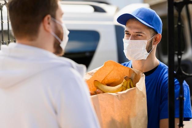フェイスマスクで食料品を提供する若い男