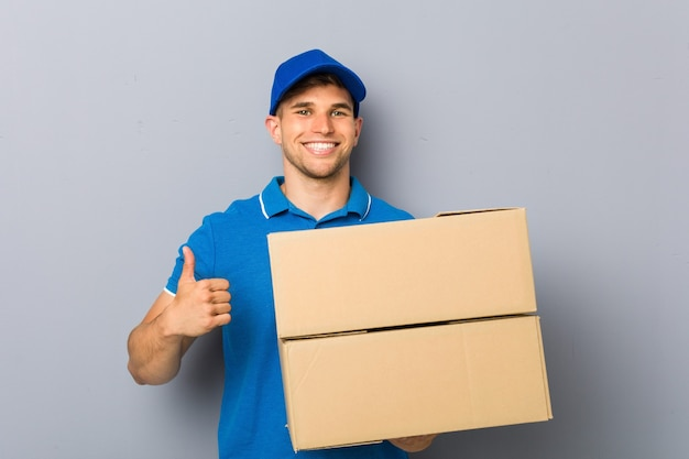 Молодой человек доставляет пакеты, улыбаясь и поднимая палец вверх