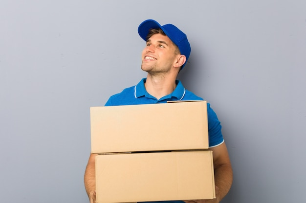 Young man delivering packages smiling confident with crossed arms.