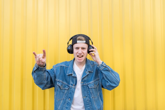Young man in a denim jacket is listening to rock in his headphones and shows a sign of heavy metal.