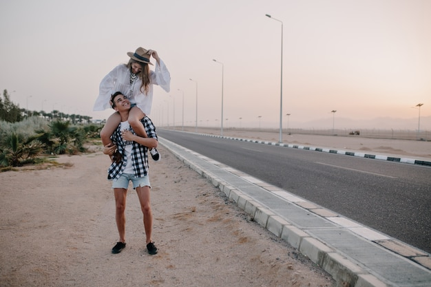 Young man in denim shorts holding his graceful girlfriend on shoulders standing near the highway. adorable woman in vintage white blouse spending time with boyfriend and having fun on outdoor date