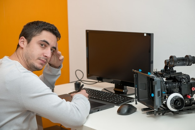 Young man designer using graphics tablet for video editing