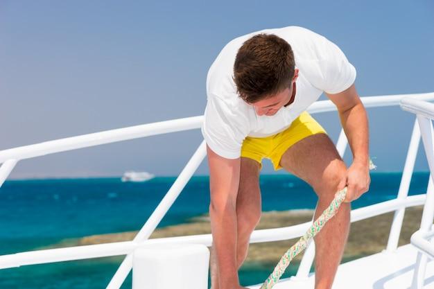 젊은 남자는 화창한 여름날 요트에 밧줄을 부지런히 고정하고 아름다운 바다를 배경으로 한다