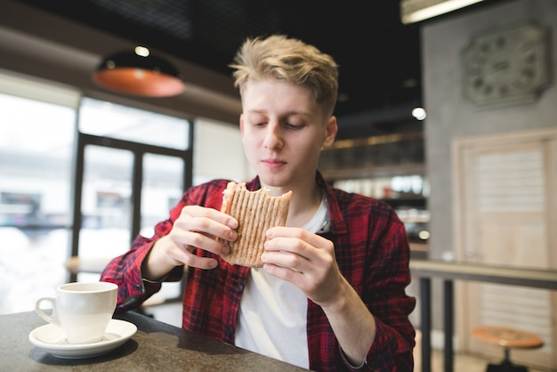 Young man dining panini sandwich in restaurant.