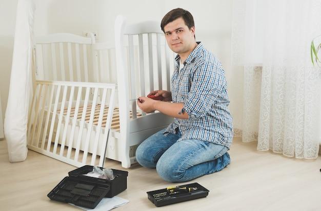 保育園で家具を分解する若い男