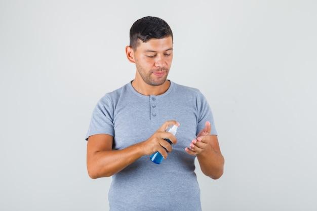 若い男が灰色のtシャツの消毒剤で手を消毒し、保護を探しています。