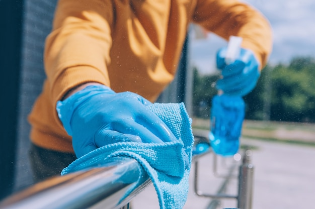 Young man disinfects a railing with a blue antiseptic and a rag in his hand