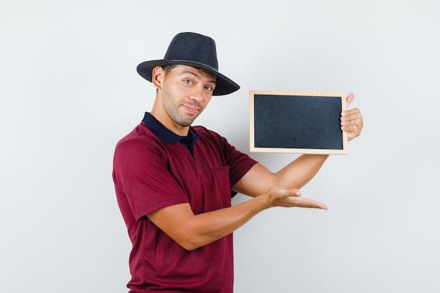 티셔츠, 모자 전면 보기에 칠판을 표시하는 젊은 남자.
