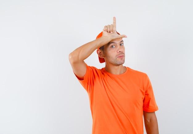 オレンジ色のtシャツとキャップの正面図で彼の額に敗者のサインを表示している若い男。
