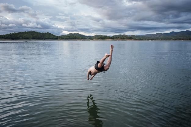 国立公園の湖に飛び込む青年