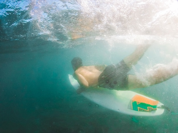 Young man diving with surfboard underwater