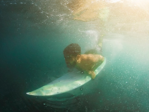Young man diving with white surfboard underwater