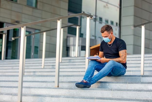 Молодой человек делает домашнее задание на ступеньках университетского городка
