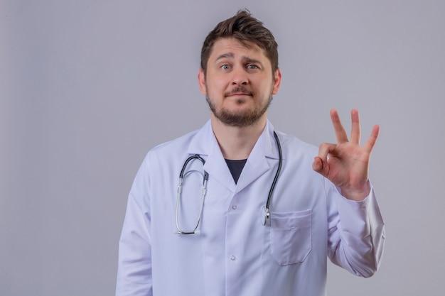 若い男医師幸せと肯定的な身に着けている白いコートと彼の指を笑顔でokの標識を示す聴診器