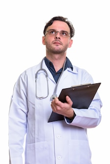 Young man doctor holding clipboard while thinking