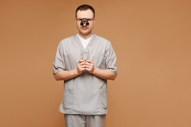Молодой человек-врач в медицинской форме и очках держит инструменты хирурга в руках и позирует на бежевом фоне изолированно. концепция здравоохранения и неотложной помощи.