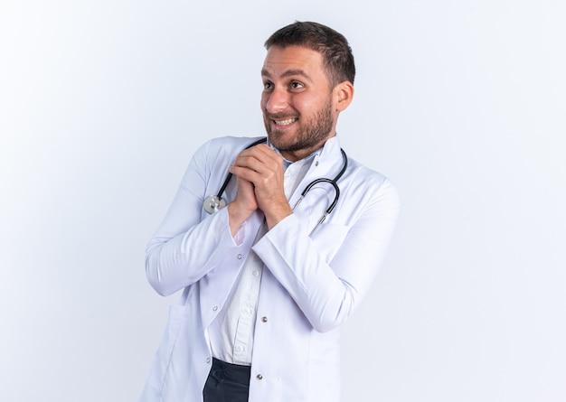 흰색 코트를 입은 젊은 남자 의사와 목에 청진기가 손을 잡고 행복하고 쾌활하게 무언가를 기다리고 있습니다.
