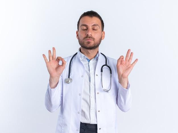 흰 코트를 입은 젊은 남자 의사와 목에 청진기를 들고 흰 벽 위에 손가락으로 서 있는 명상 제스처