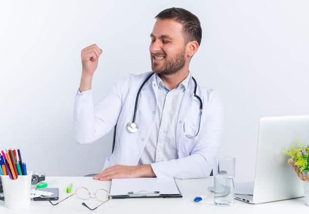 白衣を着た若い男の医者と聴診器は、白い壁の上のラップトップでテーブルに座って幸せで陽気な握りこぶしを脇に見ています
