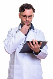 Young man doctor reading on clipboard while think