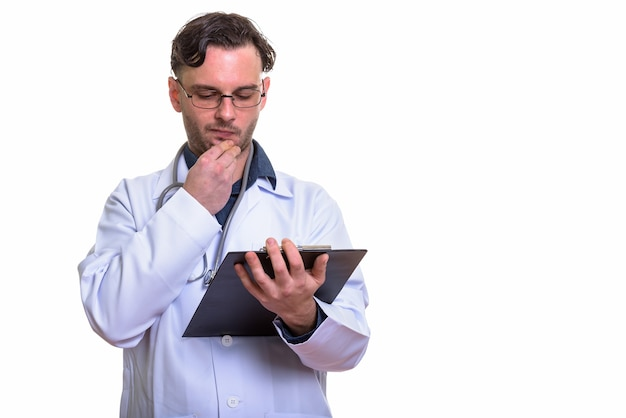 考えながらクリップボードで読む若い男の医者
