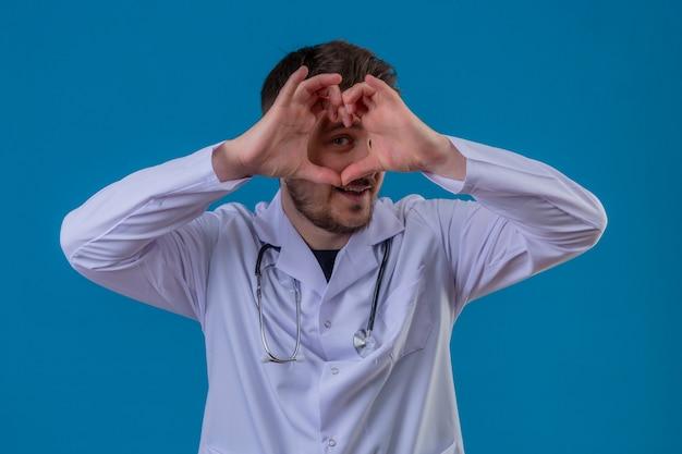 Доктор молодого человека нося белое пальто и стетоскоп делая форму сердца с рукой и пальцами усмехаясь смотрящ через знак над изолированной голубой предпосылкой