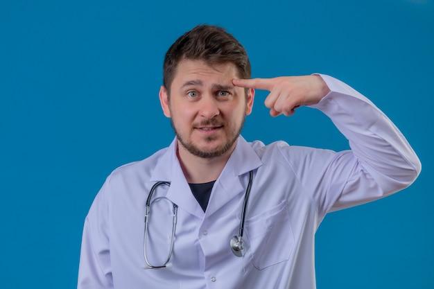 孤立した青い背景に彼の頭に混乱している人差し指を探している白衣と聴診器を着ている若い男医師