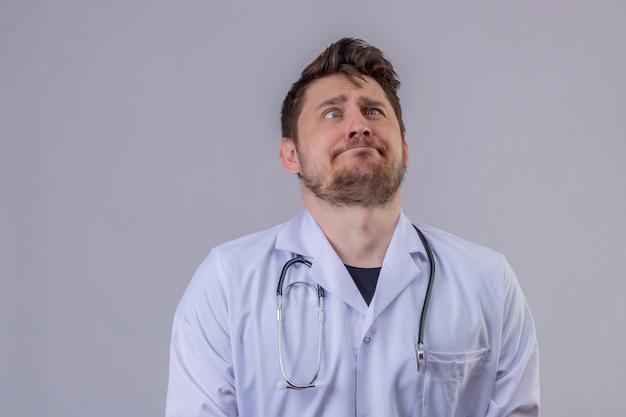 Доктор молодого человека нося белое пальто и стетоскоп делая гримасу и сумашедшее лицо над изолированной голубой предпосылкой