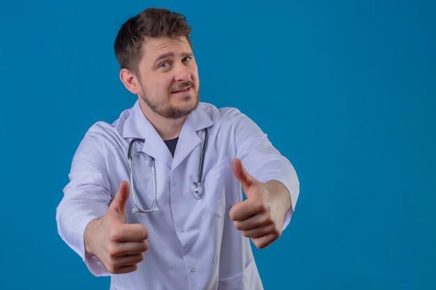白衣と分離の青い背景に幸せそうな顔でジェスチャーを親指を示す聴診器を着ている若い男医師