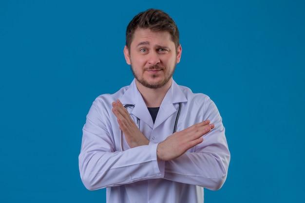 孤立した青い背景に白いコートと組んだ腕で立っている聴診器停止ジェスチャーを身に着けている若い男医師