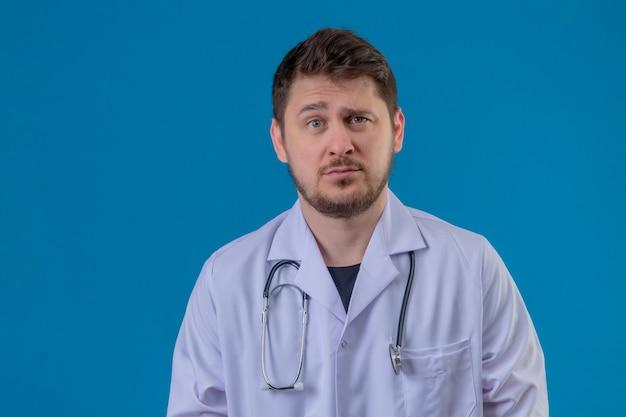 孤立した青い背景に懐疑的な表情で白いコートと聴診器立って身に着けている若い男医師