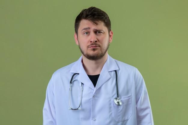 孤立した緑の背景に白衣と懐疑的な表情で聴診器立って身に着けている若い男医師