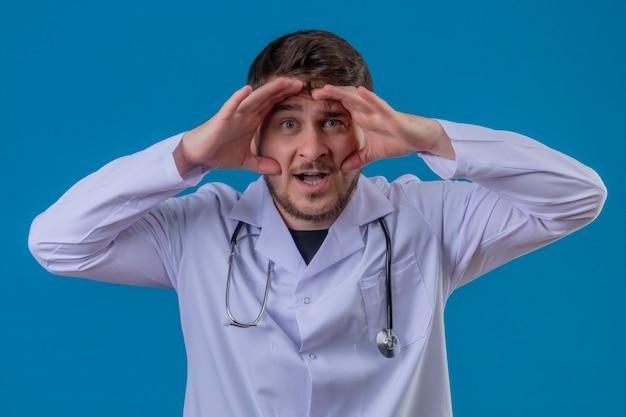 白衣と聴診器を身に着けている若い男医師驚いて分離青い背景上の頭の上の手で遠くを見て