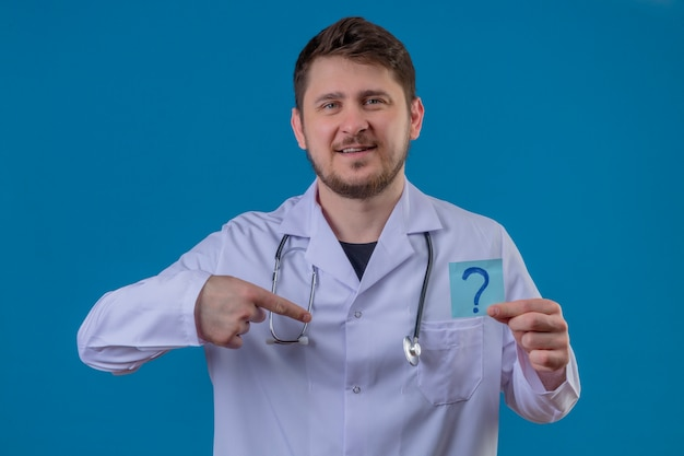 Young man doctor wearing white coat and stethoscope holding paper with question mark with smile on face pointing finger to himself over isolated blue background