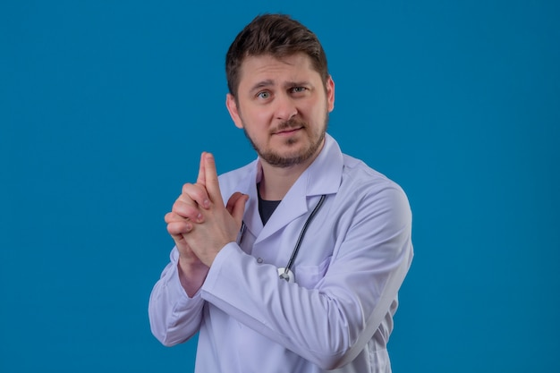 Young man doctor wearing white coat and stethoscope holding symbolic gun with hand gesture over isolated blue background