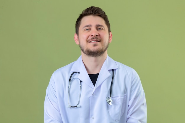 Young man doctor wearing white coat and stethoscope looking confident with smile on face over isolated green background