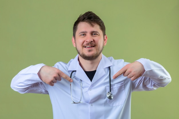 Young man doctor wearing white coat and stethoscope looking confident with smile on face, pointing oneself with fingers proud and happy over isolated green background