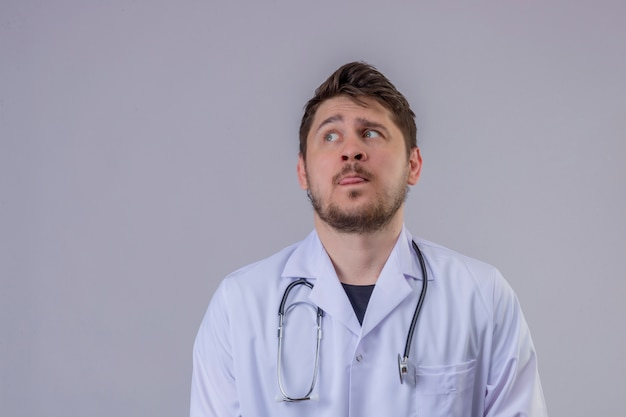 Young man doctor wearing white coat and stethoscope looking confused, sticking tongue out and thinking