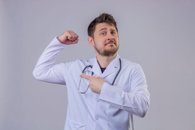 Camice d'uso e stetoscopio di medico del giovane che indicano dito la sua espressione di forza del bicipite, concetto del vincitore