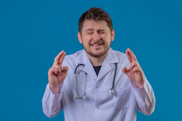 Young man doctor wearing white coat and stethoscope standing with closed eyes raising fingers crossed makes desirable wish over isolated blue background